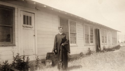 Dunn poses in front of the Chemistry Shack on ACU's campus in 1944, wearing his Commencement regalia.