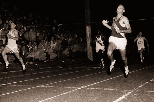 Morrow (right) breaks the finish line tape at a race on a cinder track in 1956.