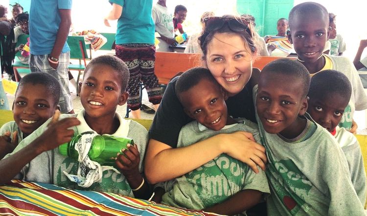 J'Lyn Emerson poses with children in Haiti.
