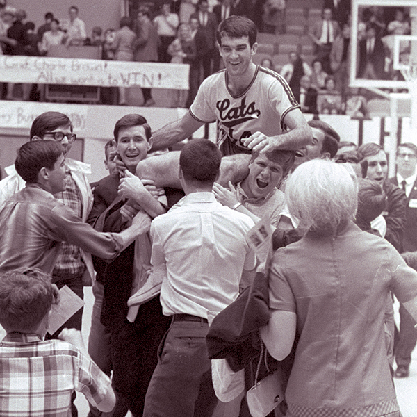 John Ray Godfrey ('68) is carried off the court by fans after setting a single-game scoring record in the first basketball game played in Moody Coliseum in 1968.