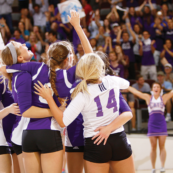 Volleyball teams members celebrate upsetting Texas Tech University in Moody in 2013.