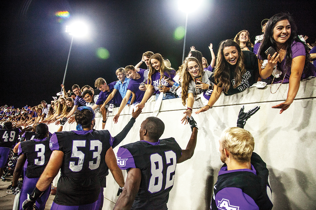 Fans line the Anthony Field walls at Wildcat Stadium to congratulate players after their Grand Opening win last fall over Houston Baptist University