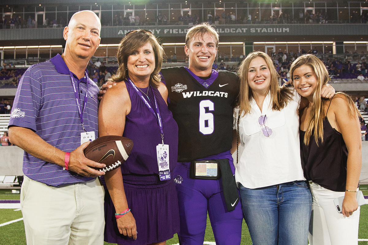 Mark and April Anthony celebrate on the field after the opening game at Anthony Field at Wildcat Stadium with their son, Luke, and their daughters, Ashlyn and Allie.