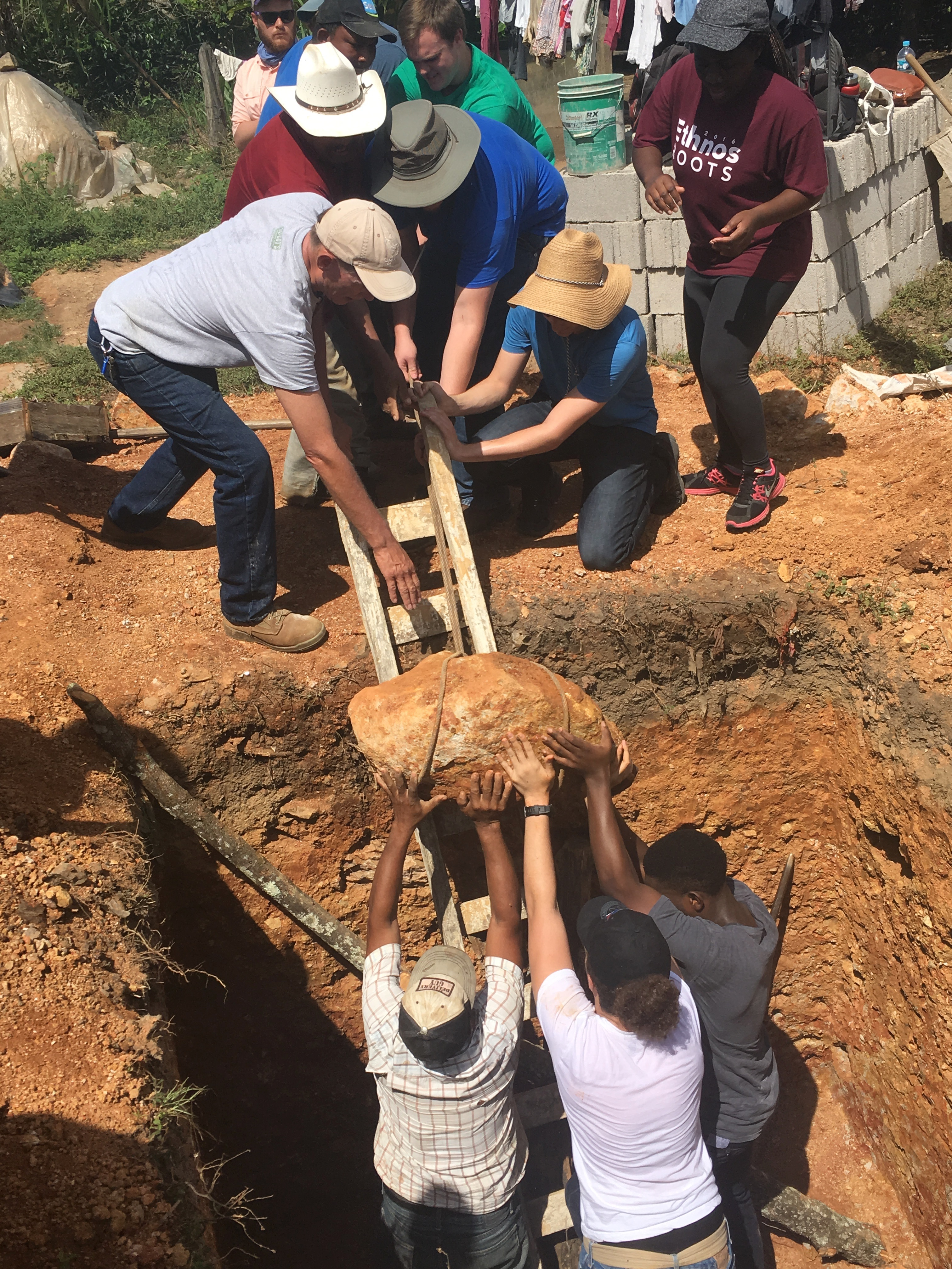 "ACU engineering and physics students work with a family in Linares to ""engineer"" a solution to get a large rock out of the latrine pit before beginning construction."