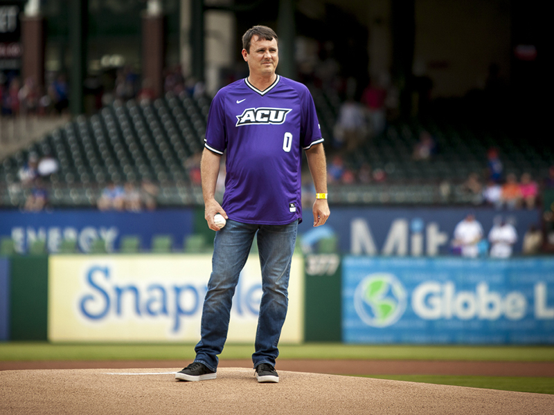ACU men's basketball coach Joe Golding on the mound at Globe Life Park