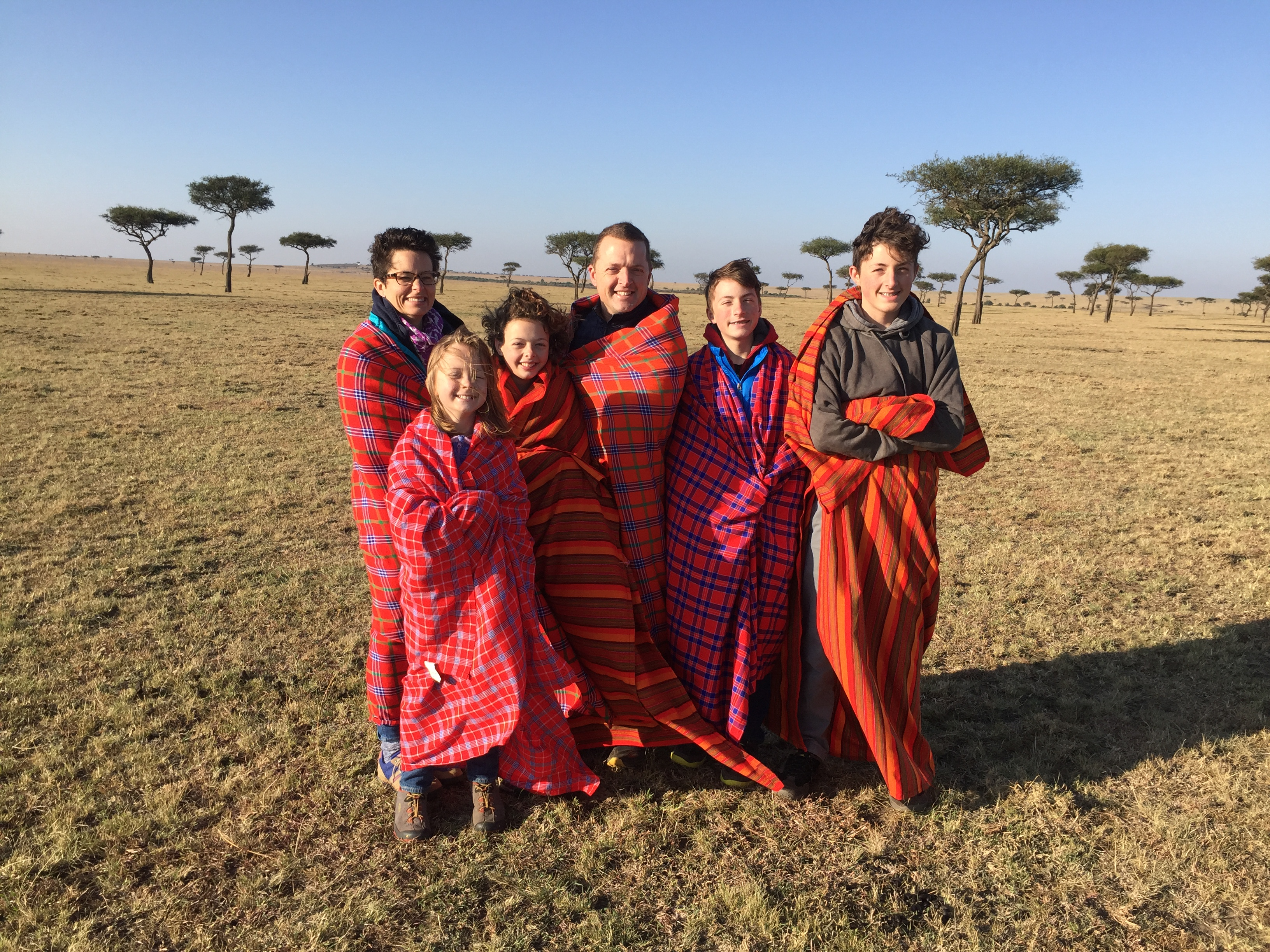 The Caire family in Africa, wrapped in traditional blankets. From left are Allison, Sarah, Annie, Will, Peter and David.