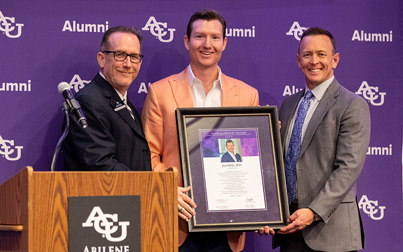 Joel Wells, M.D. ('06), is presented his 2020 Young Alumnus of the Year Award by Craig Fisher (left), and Dr. Phil Schubert.