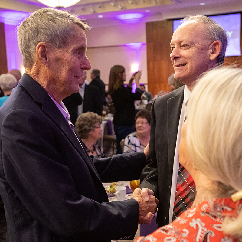 A. Don Drennan ('58) greets Wes Kittley ('81), ACU's 2020 Outstanding Alumnus of the Year, at the Alumni Day luncheon Feb. 23.