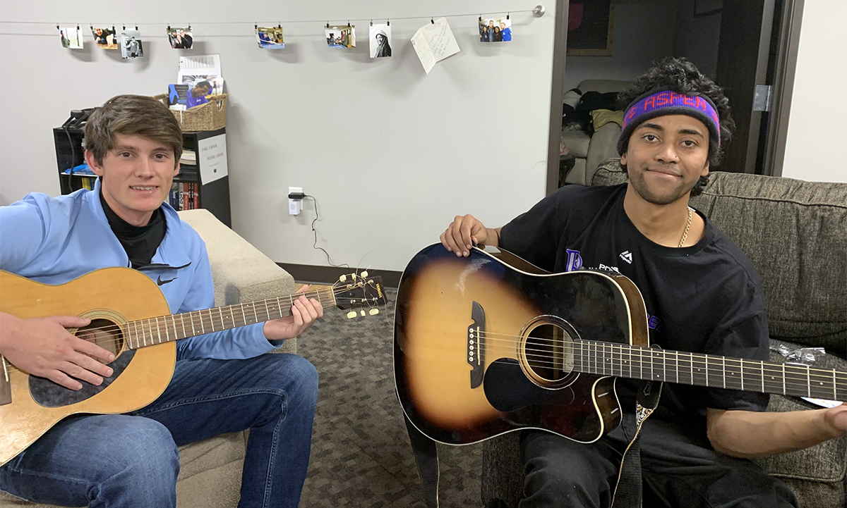 Andrew Sawyer (left), sophomore biochemistry major, and a Dry Bones friend enjoy an impromptu guitar session while hanging out at the ministry's headquarters.