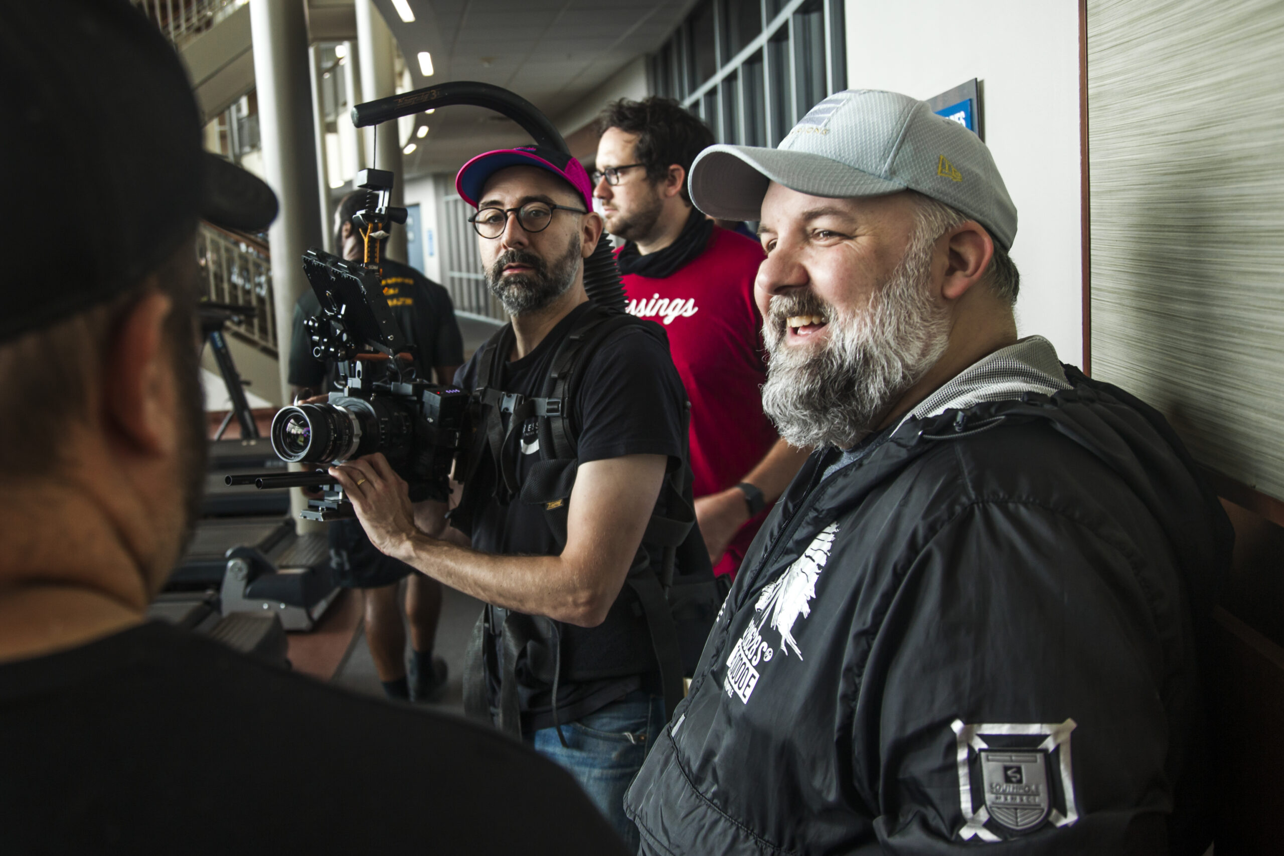 Randy Brewer (far right) talks with film crew Joshua Wann (with camera) and director Nate Corrona (far left) at Craig Ranch Fitness and Spa in McKinney, Texas.